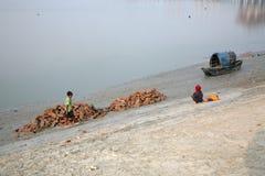 Barche dei pescatori incagliati nel fango a bassa marea sulla città d'inscatolamento vicina di Malta del fiume, India Fotografie Stock Libere da Diritti