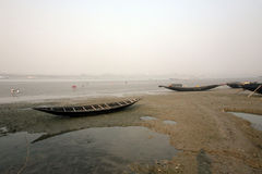 Barche dei pescatori incagliati nel fango a bassa marea sulla città d'inscatolamento vicina di Malta del fiume, India Fotografia Stock