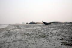 Barche dei pescatori incagliati nel fango a bassa marea sulla città d'inscatolamento vicina di Malta del fiume, India Immagini Stock Libere da Diritti