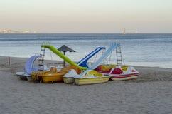 Barche del pedale con gli acquascivoli sulla sabbia della spiaggia al tramonto Immagini Stock Libere da Diritti