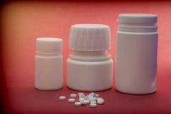 Barche delle pillole bianche con le compresse bianche dei tipi differenti isolati su Backgrou rosso Fotografia Stock Libera da Diritti