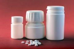 Barche delle pillole bianche con le compresse bianche dei tipi differenti isolati su Backgrou rosso Immagini Stock
