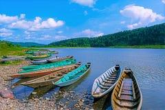 Barche di legno attraccate alla banca del fiume Fotografie Stock
