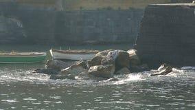 Barche di legno che galleggiano vicino alla base del castello, onde che si schiantano contro le pietre stock footage