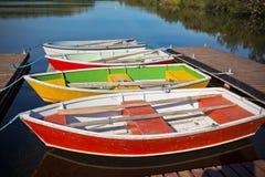 Barche di legno di galleggiamento di colore con le pagaie in un lago Fotografia Stock Libera da Diritti