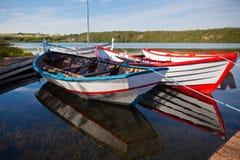 Barche di legno di galleggiamento di colore con le pagaie in un lago Immagini Stock Libere da Diritti