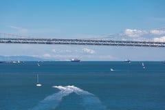 Barche e Jet Skis Under Bay Bridge Immagini Stock Libere da Diritti