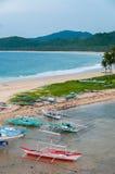 Barche e palme alla spiaggia di sabbia davanti a Fotografie Stock