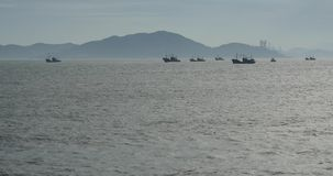 barche 4k che galleggiano nel mare contro il fondo dell'isola, gru distante del cantiere navale video d archivio