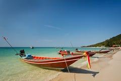 Barche lunghe locali tailandesi di racconto alla spiaggia sotto chiaro cielo blu fotografia stock