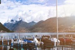 Barche nel porto sul lago con una vista delle montagne e del cielo con il nuvola-viaggio voluminoso, sfondo naturale Fotografie Stock Libere da Diritti