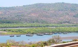 Barche in piccolo porto nel trotto del fiume in Anjarle - il paesaggio di Konkan fotografia stock libera da diritti