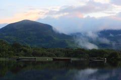Barche sul lago al piede della montagna fotografie stock libere da diritti