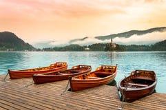 Barche sul lago Bled in Slovenia Lago mountain con la piccola isola, la chiesa ed il cielo variopinto, alba stilizzata Fotografia Stock Libera da Diritti