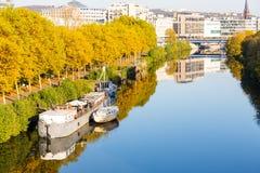 Barche sulla passeggiata vicina del fiume che conduce al centro urbano con lo shoppi immagine stock