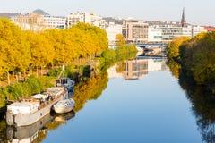 Barche sulla passeggiata vicina del fiume che conduce al centro urbano con lo shoppi fotografie stock libere da diritti
