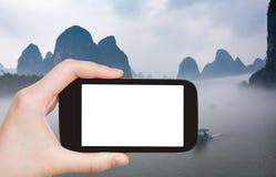 barche turistiche dei photograps in nebbia in Yangshuo Fotografia Stock