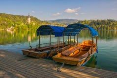 Barche turistiche di legno attraccate al pilastro sul lago Bled, Slovenia fotografia stock