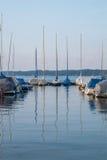Barche variopinte di parcheggio su un lago Immagini Stock