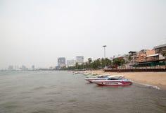 Barche variopinte su una spiaggia un giorno nebbioso nuvoloso Fotografia Stock