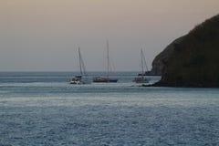 Barche a vela ancorate al crepuscolo in una baia di un'isola tropicale, Figi immagini stock libere da diritti