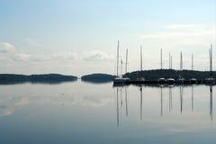 Barche a vela che galleggiano nel lago blu di estate Fotografia Stock