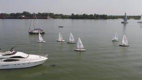Barche a vela che galleggiano sull'acqua blu del lago Sport della concorrenza della navigazione Yacht e belle viste sul mare stock footage
