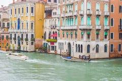 Barche a vela della gente e taxi dell'acqua accanto alle costruzioni veneziane gotiche un giorno piovoso di novembre sul canale n fotografia stock