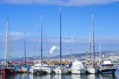 Barche a vela di parcheggio nel porto sui precedenti della città di Atene, Grecia immagine stock