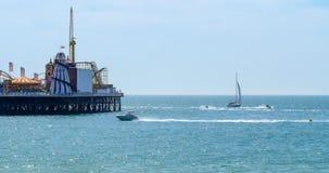 Barche a vela e jet ski dell'acqua al pilastro di Brighton Immagini Stock Libere da Diritti