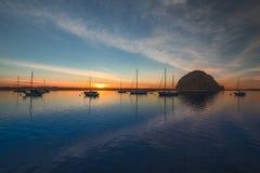 Barche a vela e roccia di Morro al tramonto immagini stock libere da diritti