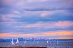 Barche a vela nel mare contro lo sfondo delle costruzioni della città Fotografia Stock