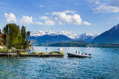 Barche a vela in porto al infornt di Thun del lago della montagna delle alpi Immagini Stock