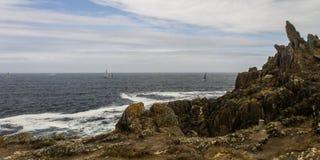 Barche a vela un giorno nuvoloso vicino alla riva appuntita fotografia stock