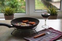 Barchelor frukost - stekte ägg med korvar på en teflonstekpanna med exponeringsglas av vin arkivfoto