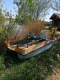 Barco abandonado ao lado de um lago fotografia de stock