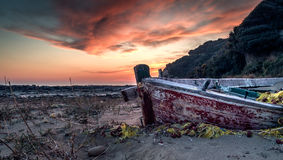 Barco abandonado contra la puesta del sol Foto de archivo