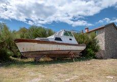 Barco abandonado en casa de la piedra de la orilla en fondo Imagen de archivo libre de regalías