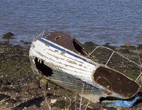 Barco abandonado y varado con un casco dañado Fotografía de archivo