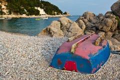 Barco al revés en la playa rocosa Foto de archivo libre de regalías