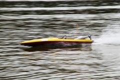 Barco amarillo de RC que apresura en un lago Fotos de archivo libres de regalías