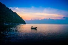 Barco amarrado cerca de la costa en la salida del sol Imagen de archivo libre de regalías