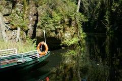 Barco amarrado en la orilla del río en bosque Fotos de archivo