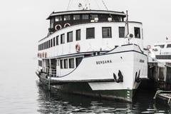 Barco amarrado en un día de invierno de niebla Imagenes de archivo