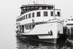 Barco amarrado en un día de invierno de niebla Foto de archivo