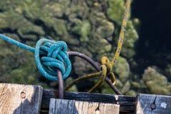 Barco amarrado a la caña de pescar Cuerda del amarre atada gravemente en el m imagenes de archivo