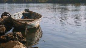 Barco amarrado viejo en un río, con los árboles en el otro lado almacen de metraje de vídeo