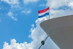 Barco anclado de la travesía con una bandera holandesa Imágenes de archivo libres de regalías