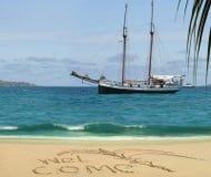Barco antiguo y recepción de la travesía en la playa tropical. Fotografía de archivo