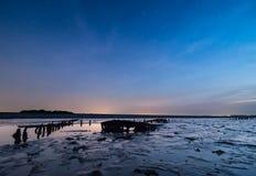 Barco arruinado viejo con puesta del sol y las estrellas Foto de archivo